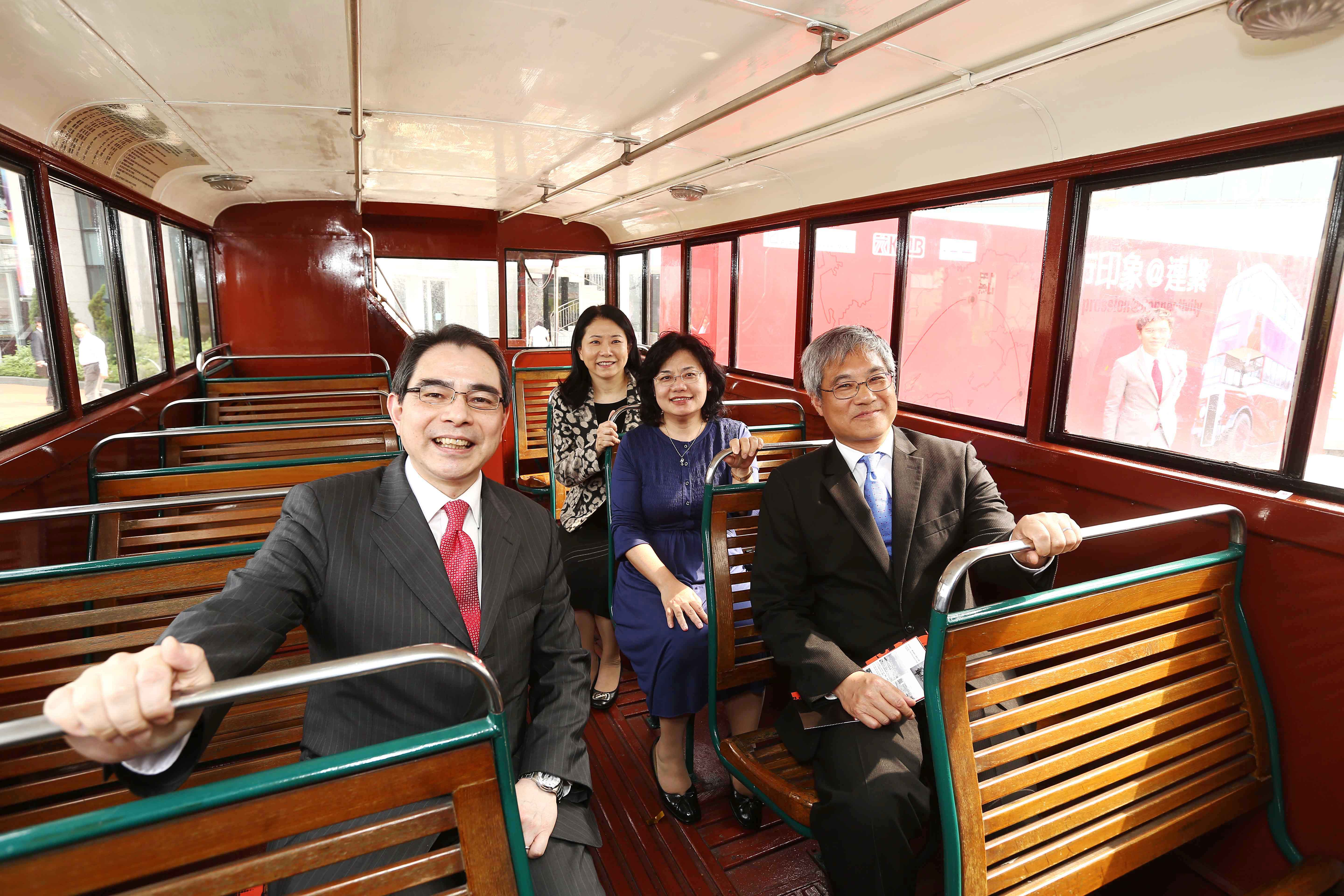 The four officiating guests on the upper deck of the vintage Daimler A bus.